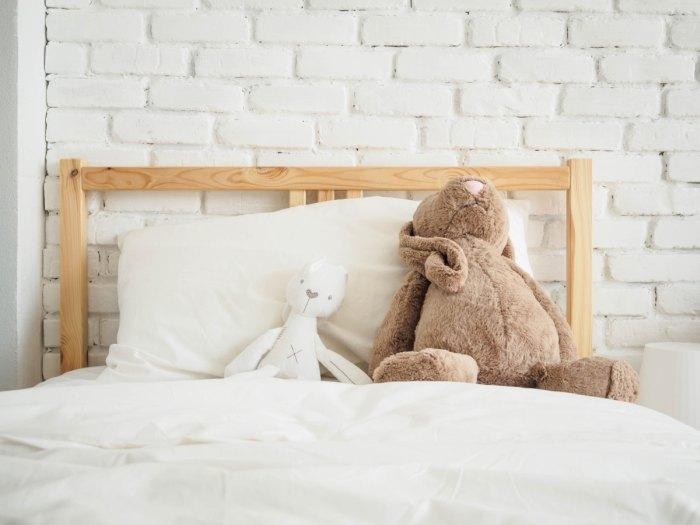 detská posteľ na ktorej sú plyšové hračky