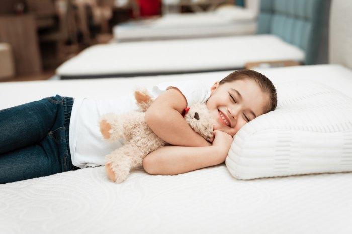 usmievajúce, spokojné dieťa spí na posteli, ktorá má matrac s pamäťovou penou